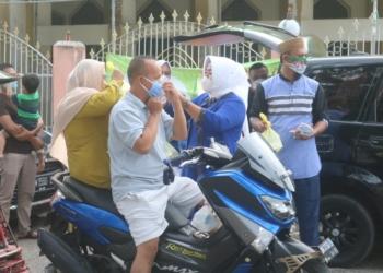 Ketua IWAPI Suharsi Igirisa yang juga Wakil Bupati Pohuwato membagikan masker dan ta'jil kepada pengguna jalan di Marisa, Senin (10/5/2021).(f.hms)