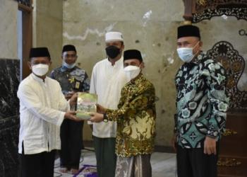 Ketua DMI Provinsi Gorontalo, Nelson Pomalingo menyerahkan 3 buah buku Khutbah Jumat kepada Ketua DMI Kabupaten Boalemo, Yakob Musa.(F.HMS)