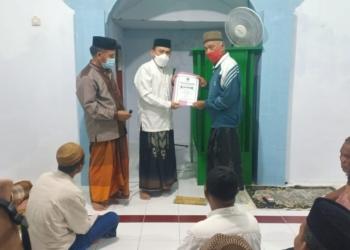 Ketua DPRD Boalemo, Karyawan Eka Putra Noho menyerahkan bantuan hibah Pemkab Boalemo secara simbilos untuk renovasi Masjid Al-Bahri Desa Pentadu Barat.(F.Narto/NewsNesia.id)