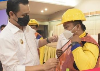 Waki Wali Kota Gorontalo, Ryan F Kono saat memakai rompi keselamatan pada salah satu tenaga kerja kontruksi. (istimewa/nn)